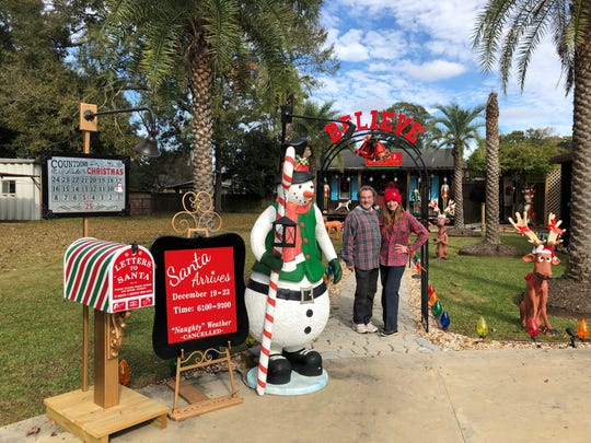 A.J. and Vanessa Miller stand outside their home that every year transforms into Santa's Workshop on Antigua Drive.