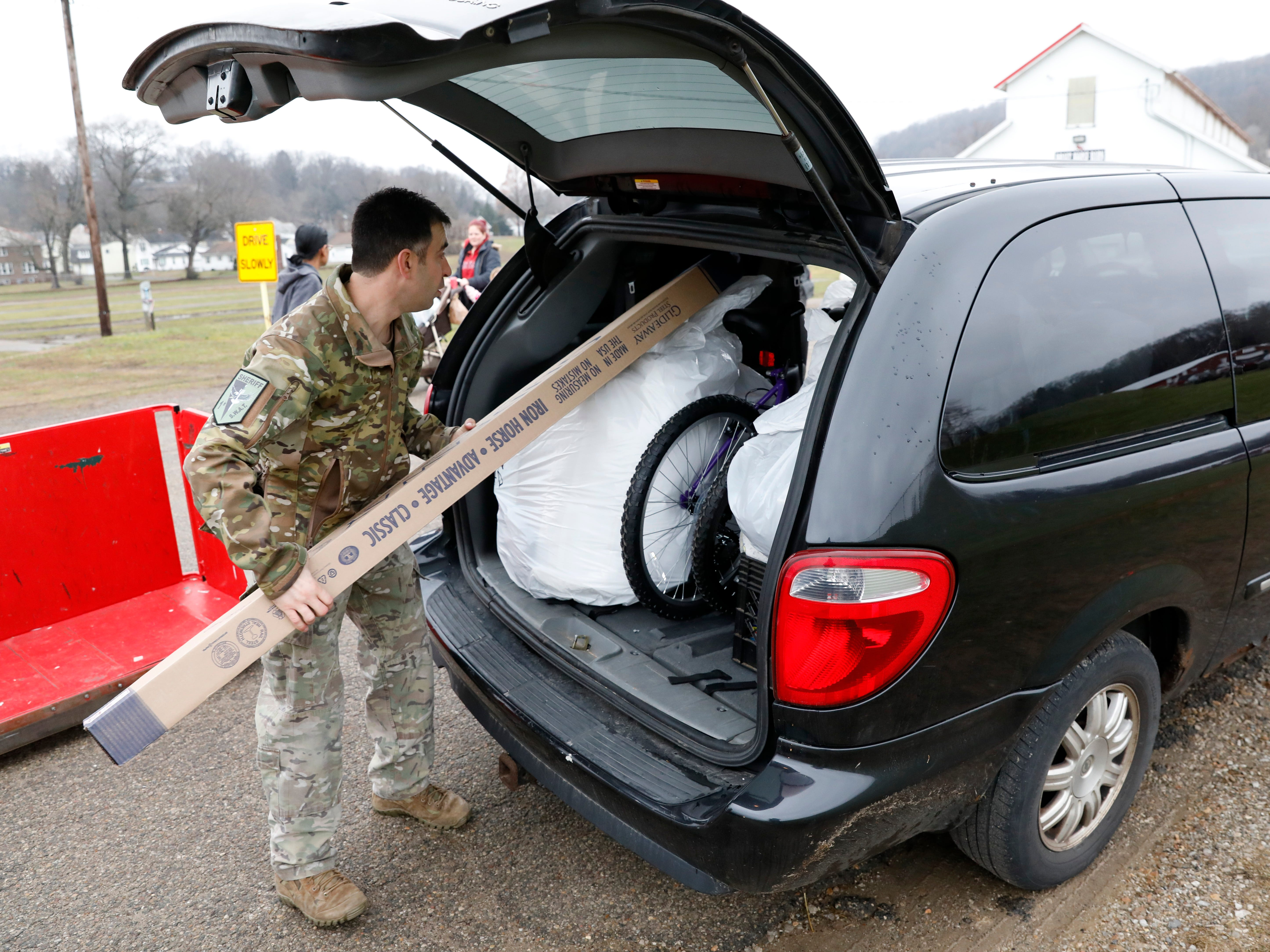 Fairfield County Sheriff's Office Sgt. Jesse Hendershot slides a bed frame into the back of a van Friday morning, Dec. 21, 2018, at Fairfield County Fairgrounds. Hendershot and other members of the sheriffs office S.W.A.T. team helped carry presents to recipient's vehicles during the Salvation Army of Fairfield County's Christmas Cheer gift distribution. More than 800 children received presents, including beds and bicycles, through the program.