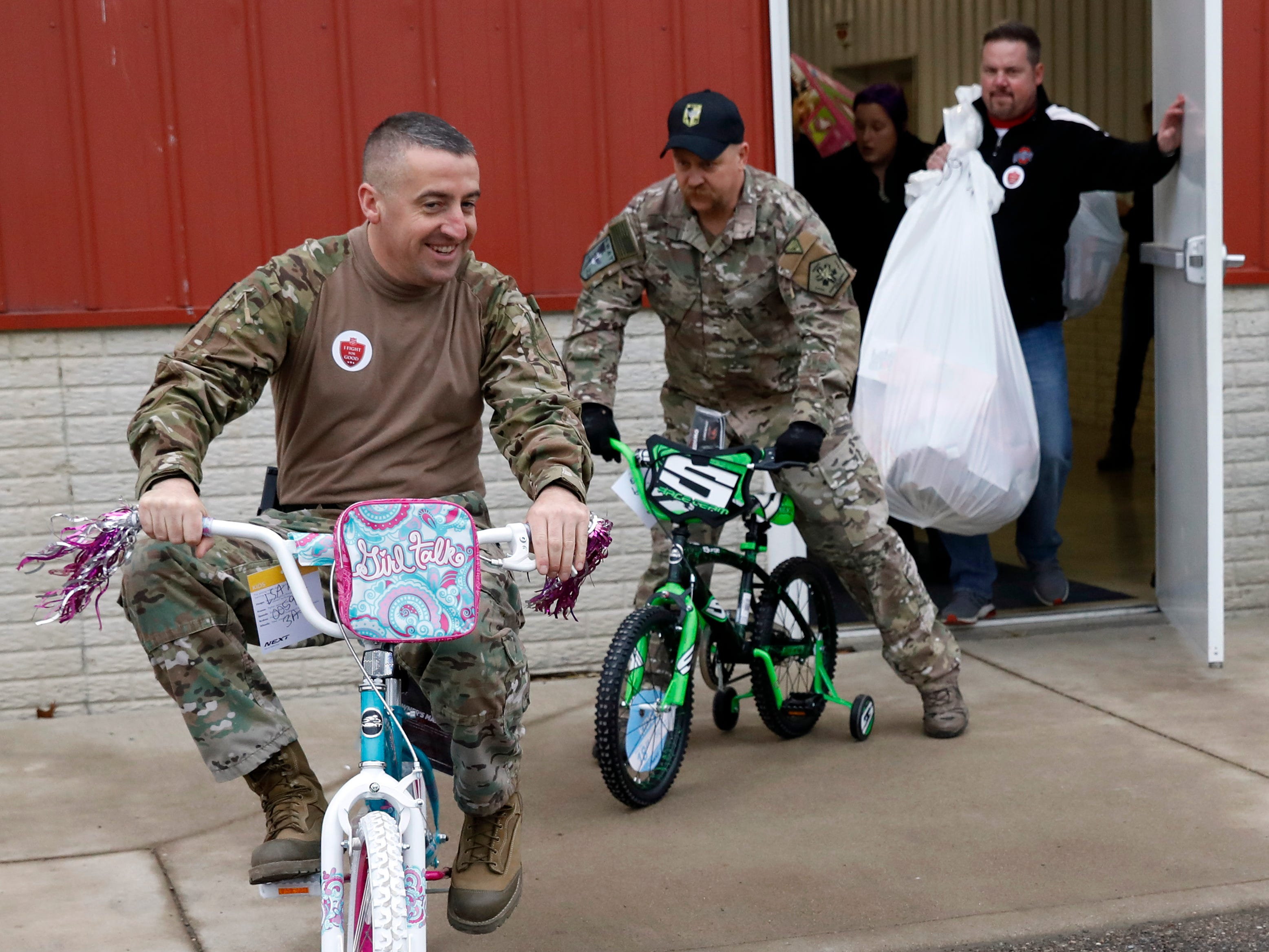 Fairfield County Sheriff's Office S.W.A.T. team members T.J. Strawn and John Lambrecht ride bicycles out of the Ed Sands building Friday, Dec. 21, 2018, at the Fairfield County Fairgrounds in Lancaster. Strawn, Lambrecht and other members of the sheriffs office S.W.A.T. team helped carry presents to recipient's vehicles during the Salvation Army of Fairfield County's Christmas Cheer gift distribution. More than 800 children received presents, including beds and bicycles, through the program.
