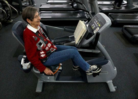 Ginny Casto reads as she works out Friday morning, Dec. 21, 2018, at the Robert K. Fox Family Y.M.C.A. in Lancaster.