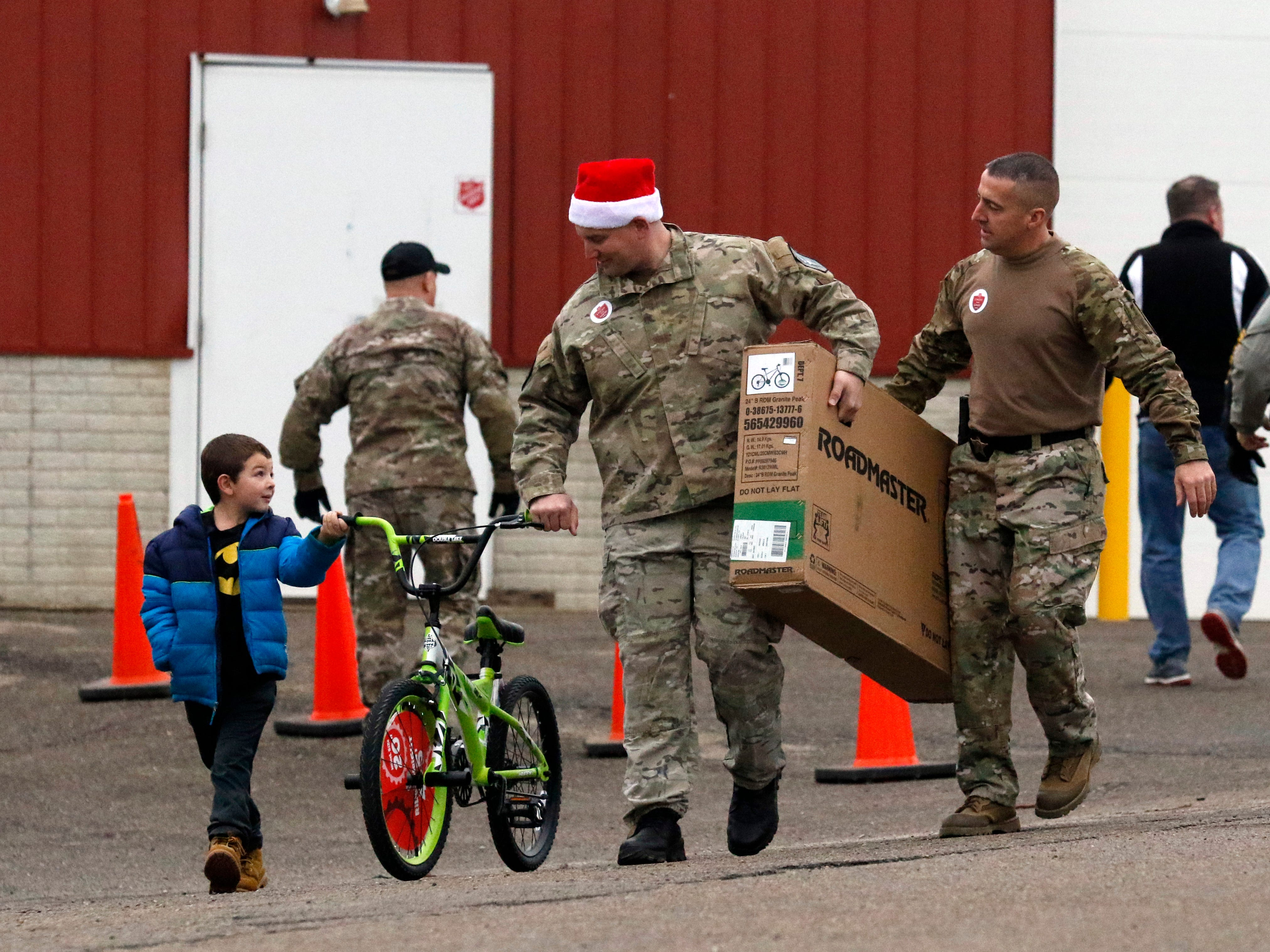 Robert Synder, 6, left, talks to Fairfield County Sheriff's Deputies Shawn Meloy, center, and T.J. Strawn Friday morning, Dec. 21, 2018, as they walk bicycles to Josh Wade and Mindy Wade's truck at the Fairfield County Fairgrounds. The bicycles and other presents were from the Salvation Army of Fairfield County's annual Christmas Cheer donation drive. This year's drive collected presents for more than 800 children throughout the county. Members of the sheriff's office S.W.A.T. helped carry gifts to recipient's vehicles.