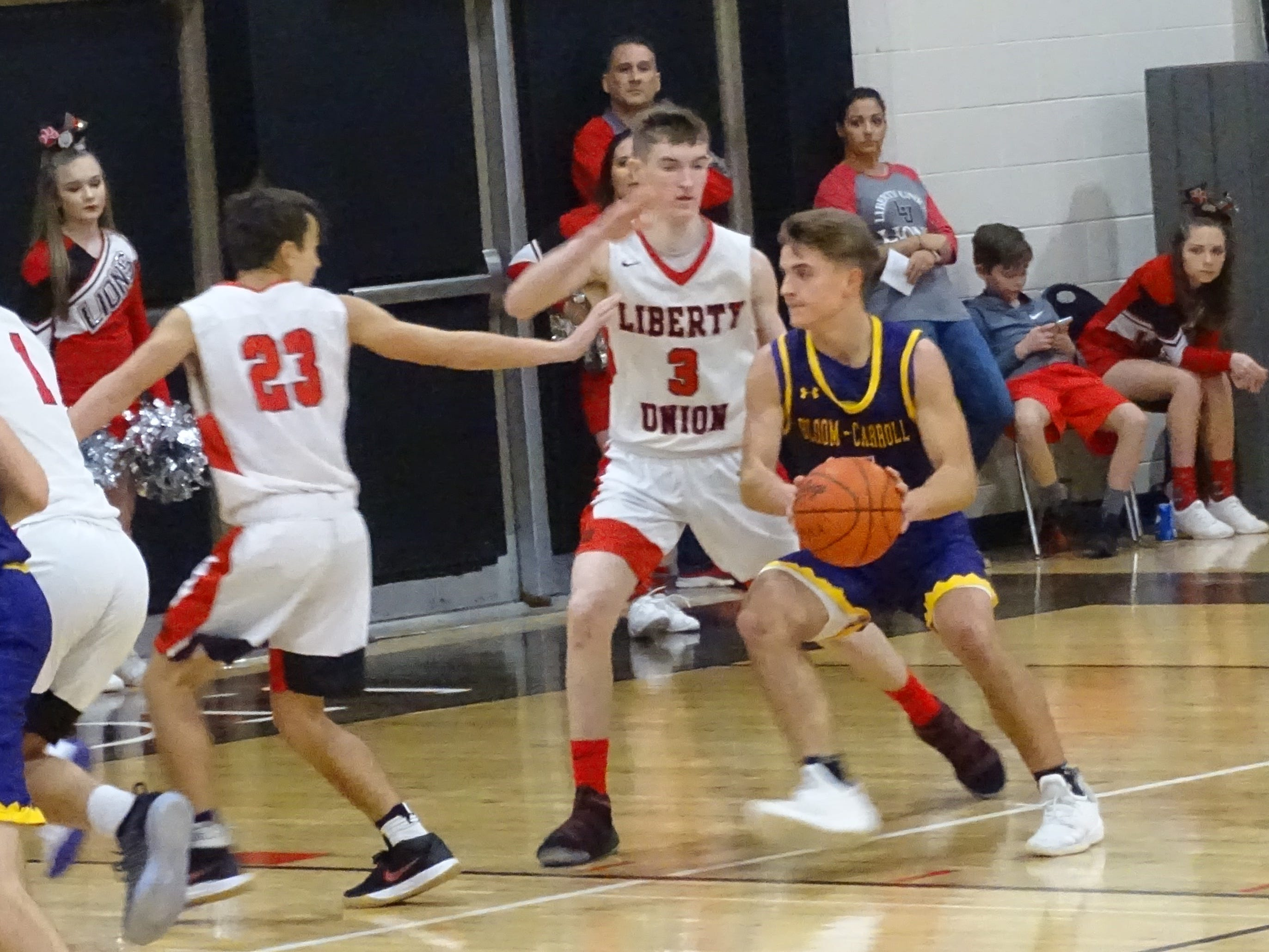 Bloom-Carroll's Josh Evans takes ball inside against Liberty Union's Jacob BerleKamp (3) and Ty Boggs (23) during the Lions' 74-53 win Thursday night.