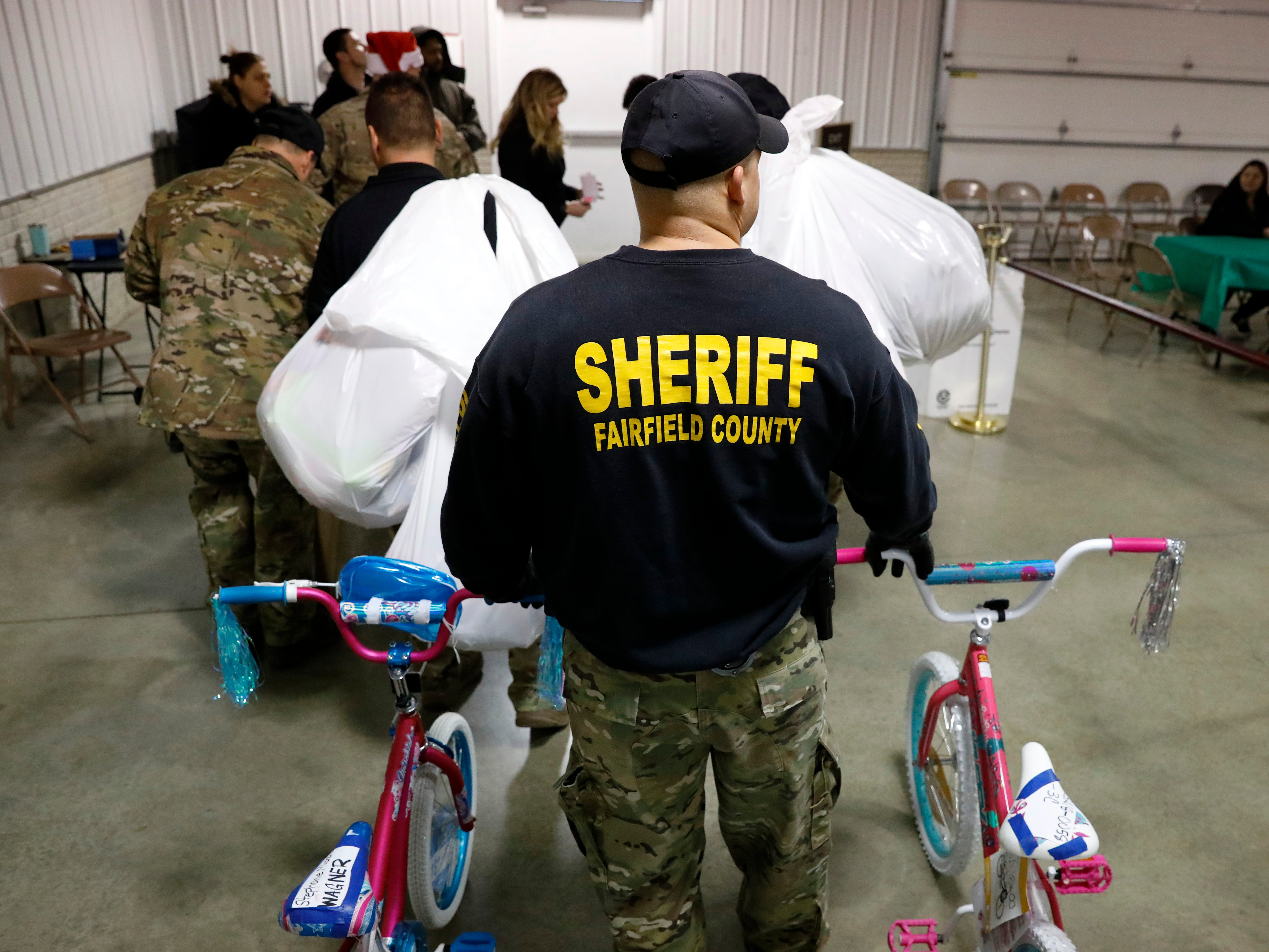 Members of the Fairfield County Sheriff's Office S.W.A.T. team help carry out presents to recipients' vehicles Friday, Dec. 21, 2018, during the Salvation Army of Fairfield County's Christmas Cheer distribution day at the Fairfield County Fairgrounds in Lancaster. This year volunteers donated gifts for more than 800 children throughout Fairfield County through the Salvation Army.