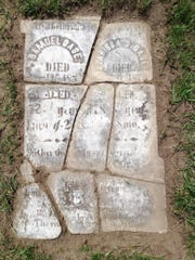 Pieces of a headstone found nearly totally buried in the ground at Old Village Cemetery took over 80 hours to reconstruct and put upright.