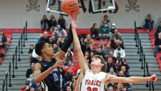 Lincoln's Emoni Bates and Pinckney's Nick Hayes battle for the opening tip in the Railsplitters 75-53 victory over the Pirates Thursday December 20, 2018 in Pinckney.