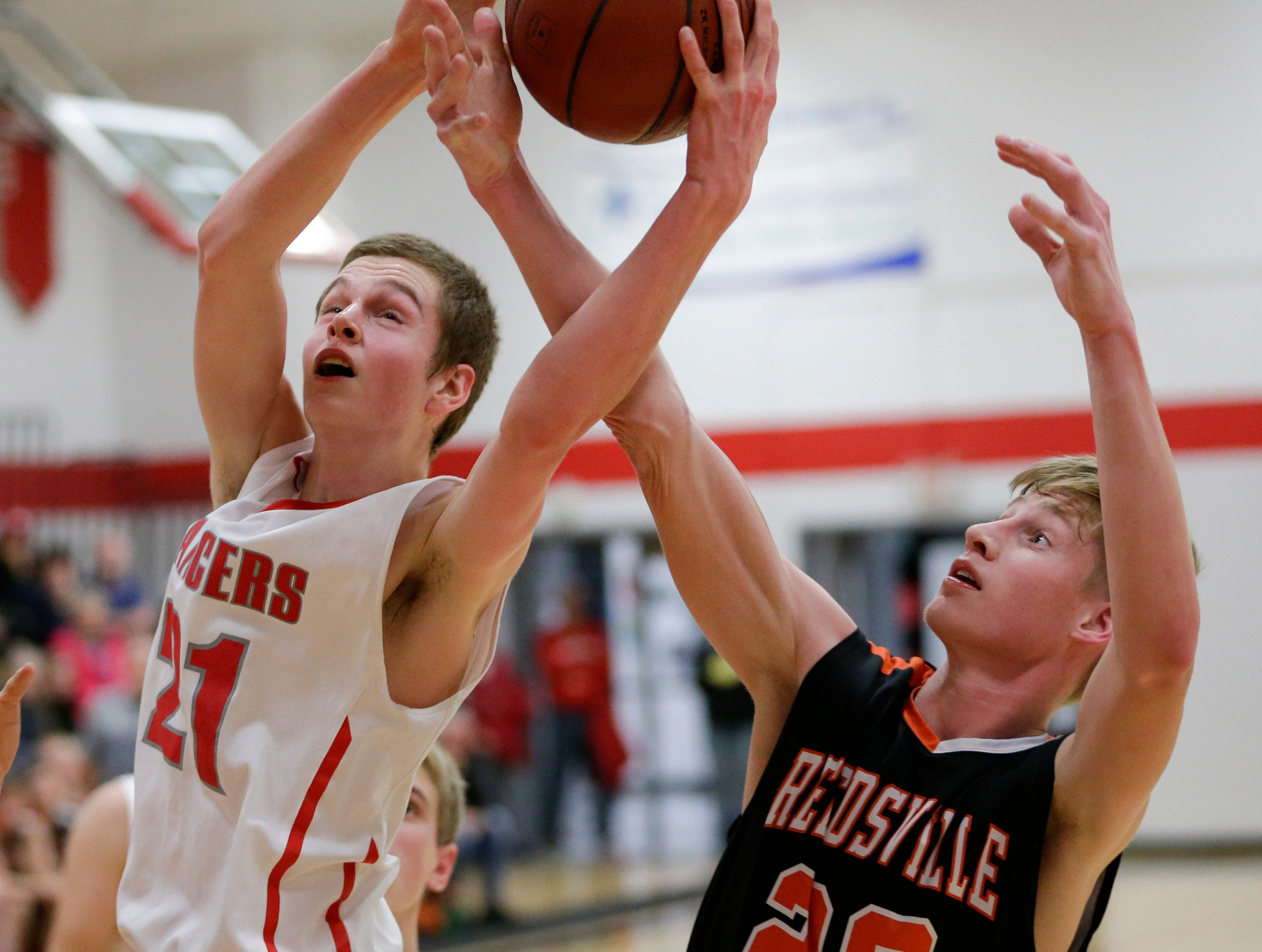 Reedsville's Cade Hafkey swipes a rebound from Manitowoc Lutheran's Kaleb Engelbrecht at Manitowoc Lutheran High School Thursday, December 20, 2018, in Manitowoc, Wis. Joshua Clark/USA TODAY NETWORK-Wisconsin