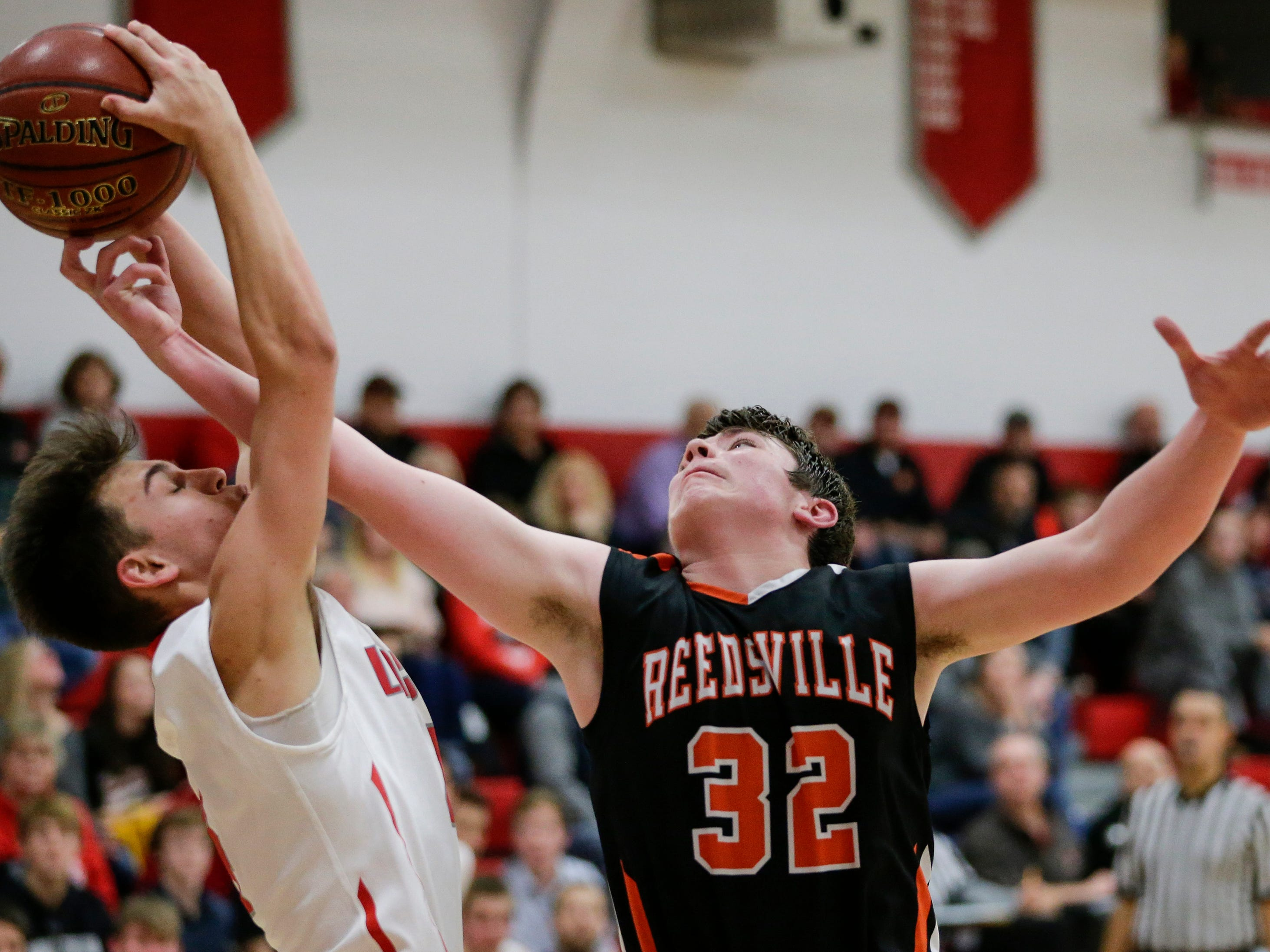 Reedsville's Micheal Brandt swipes a rebound from Manitowoc Lutheran at Manitowoc Lutheran High School Thursday, December 20, 2018, in Manitowoc, Wis. Joshua Clark/USA TODAY NETWORK-Wisconsin