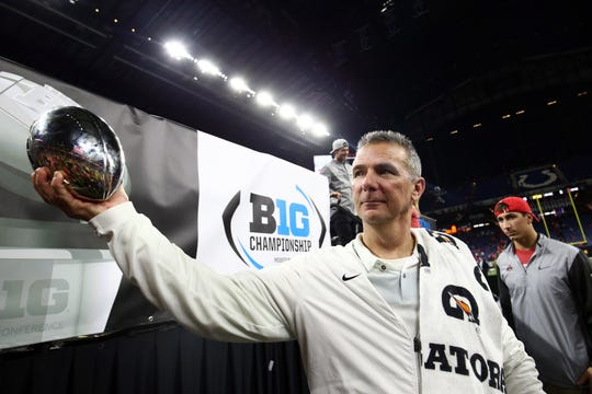 Santa Spence is giving Urban Meyer the perfect piece of clothing to make him look more like a professor.