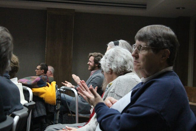 Mary Ann Doyle and other Marion residents clap after the Marion City Council unanimously votes to pay the fees to keep curbside recycling running in the city.
