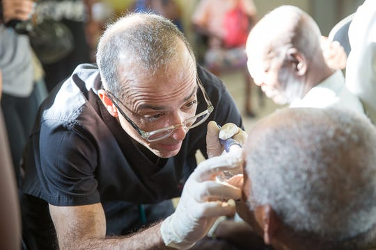 Dr. Bob Derrick, a glaucoma specialist from Dublin, examines a patient's eyes in Jamaica.