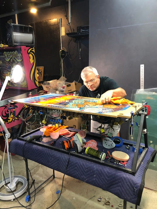 David Yopp working to restore a pinball machine in his garage workshop. He and business partner Michael Muhlert.