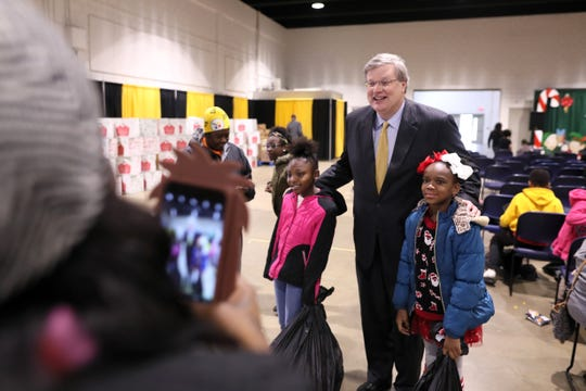 Mayor Jim Strickland and Tigers Head Coach Anfernee Hardaway join the basketball team in a Christmas toy giveaway for families gathered at the Pipkin Building at Tiger Lane on Friday, Dec. 21, 2018.