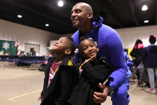 Tigers Head Coach Anfernee Hardaway poses for a photo with twins Zoey, left, and Chloe Cross, 2, during a Christmas toy giveaway for families gathered at the Pipkin Building at Tiger Lane on Friday, Dec. 21, 2018.