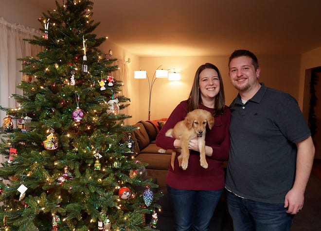 Kim and Ben Marcin, of New Berlin, hold their golden retriever puppy, Mason, in their new home. They were among those buying their first house in 2018.