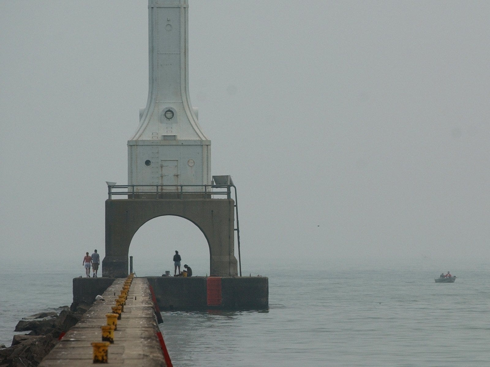 Pedestrians and fishermen are pictured near Port Washington's lighthouse in June 2002.