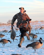 Evan Muche, 17, of Van Dyne, Wisconsin retrieves a pair of Canada geese on a hunt near Fond du Lac, Wisconsin.