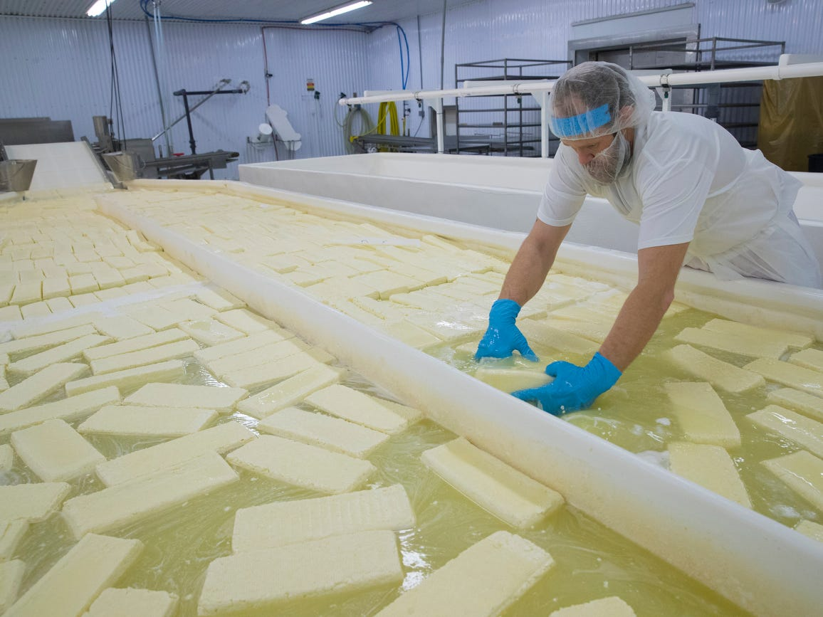 Ian Martin moves blocks of Muenster cheese through a brine solution at  K&K Cheese in Cashton.