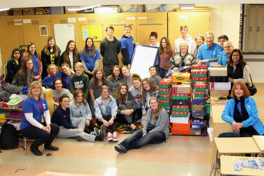 Members of Hamilton High School's Junior Optimist International, Student Council and National Honor Society groups and volunteers help pack boxes for Samaritan's Purse Operation Christmas Child.