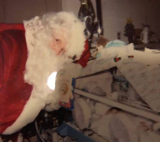 Kyle Phelps was born 12 weeks early and spent his first 98 days at St. Joseph's Hospital. His family has a happy memory, and this fading Polaroid photo, of Santa Claus showing up one day and posing with Kyle and other babies in the neonatal intensive care unit.