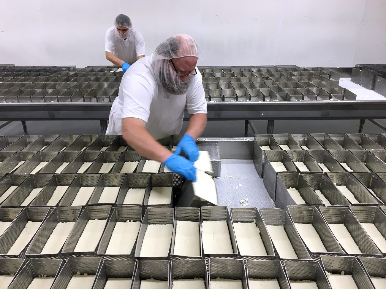 Allen Harter removes blocks of Muenster cheese from their molds at  K&K Cheese in Cashton.