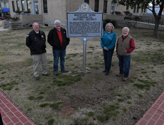Members of the Baxter County Historical & Genealogical Society (from left)  Jeff Lewis, Kevin Bodenhamer, Maryanne Edge and David Benedict pose for a photo with a sign detailing the Mountain Home Commercial Historic District on Tuesday afternoon.