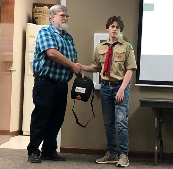 Mountain Home School Board president Neal Pendergrass receives an Automated External Defibrillator, or AED, from sophomore Ben Camp. Camp, a member of Westark Area Council Boy Scout Troop No. 156, chose to collect area donations to install 14 AEDs in buildings across the school district as part of his Eagle Scout project.