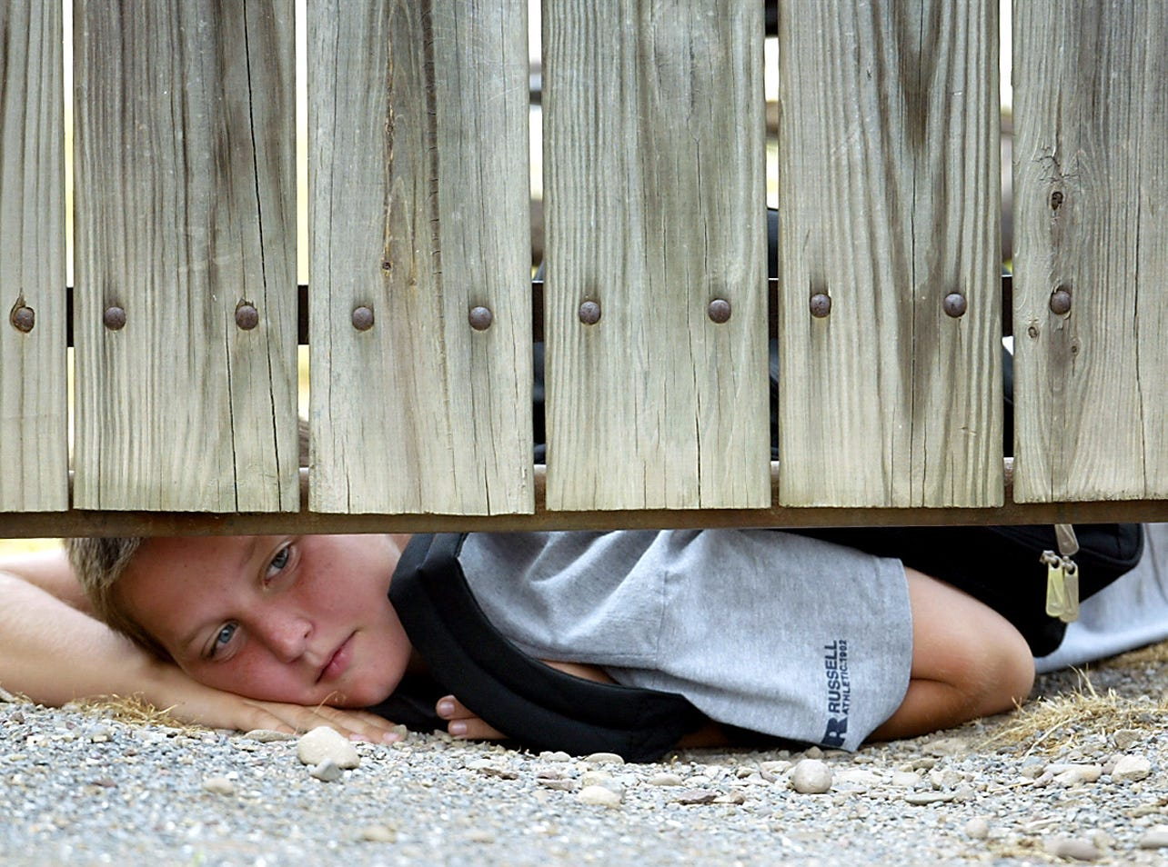 Williamsport-- June 30, 2004--Crosscutter fan Kevin Horne, 12, peeks under a fence watching the NJ Cardinals  warmup before their second game vs. the Williamsport Crosscutters. 