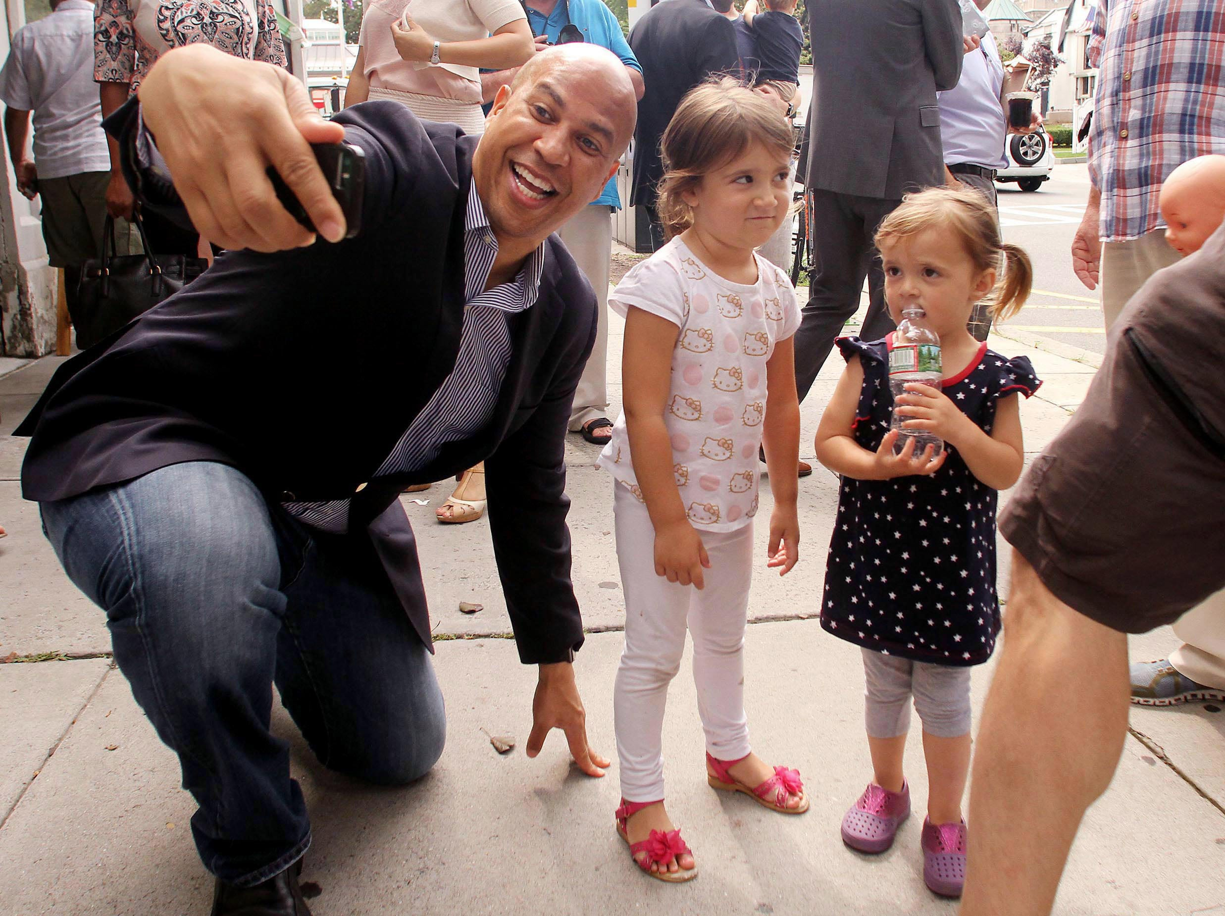 August 6, 2017--U.S. Senator Cory Booker tries unsuccessfully to get a smile while taking a selfie with a young girl during a walking tour of some of the finest small businesses in Morristown. The tour showcases a variety of businesses that all play a key role in keeping Morristown a great place to live and work.  August 5, 2017. Morristown, NJ