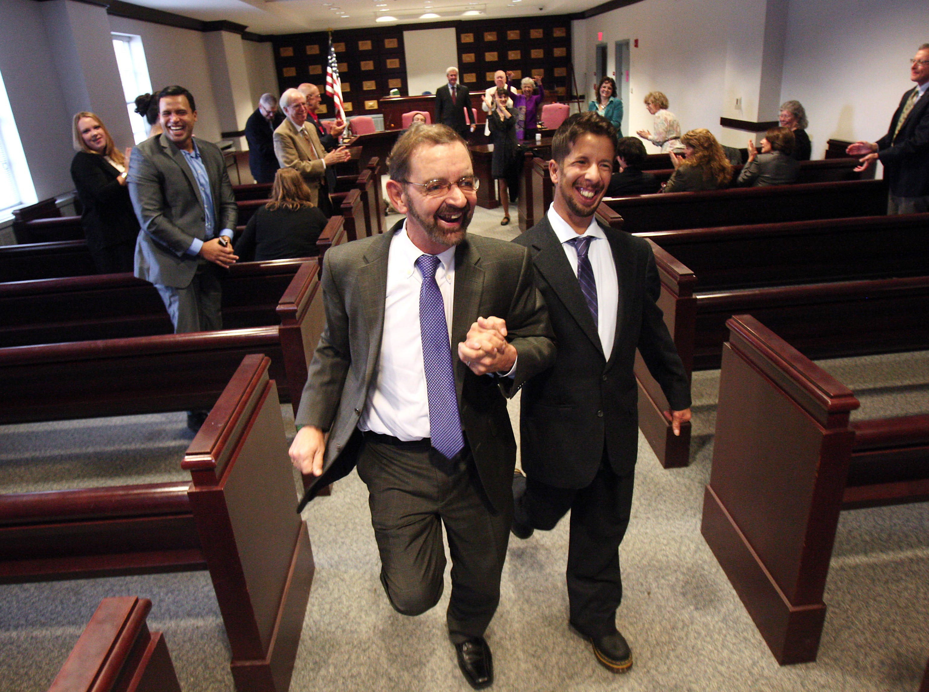 Robert Parker and Jorge Marques of Morristown run down the aisle of the council chambers in Morristown Town Hall after they were married by Mayor Tim Dougherty. Wednesday November 7, 2013, Morristown, NJ, Staff Photographer/Bob Karp