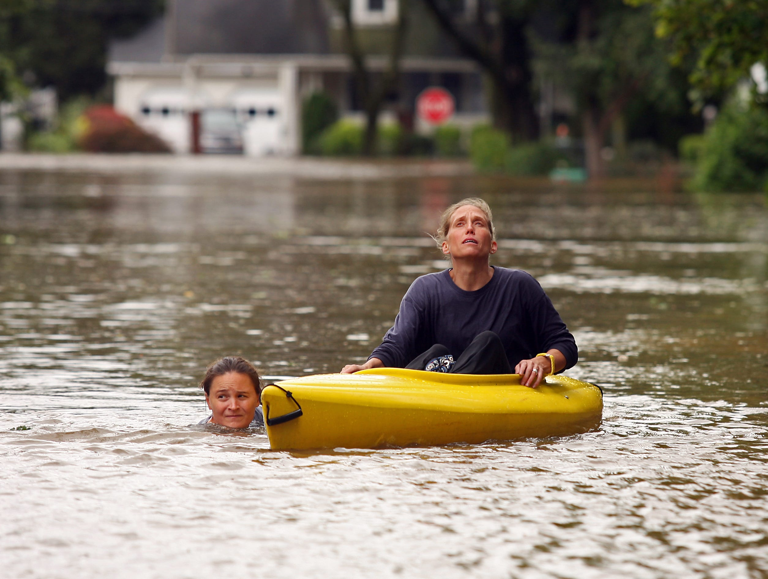 Jackie O'Connor, l, helps guide roommate Jennifer Schweizer down Hewetson Road in Denville, NJ. The two went to inspect their apartment to see the flooding damage as Hurricane Irene pounded Morris County with heavy wind and rain Sunday.
