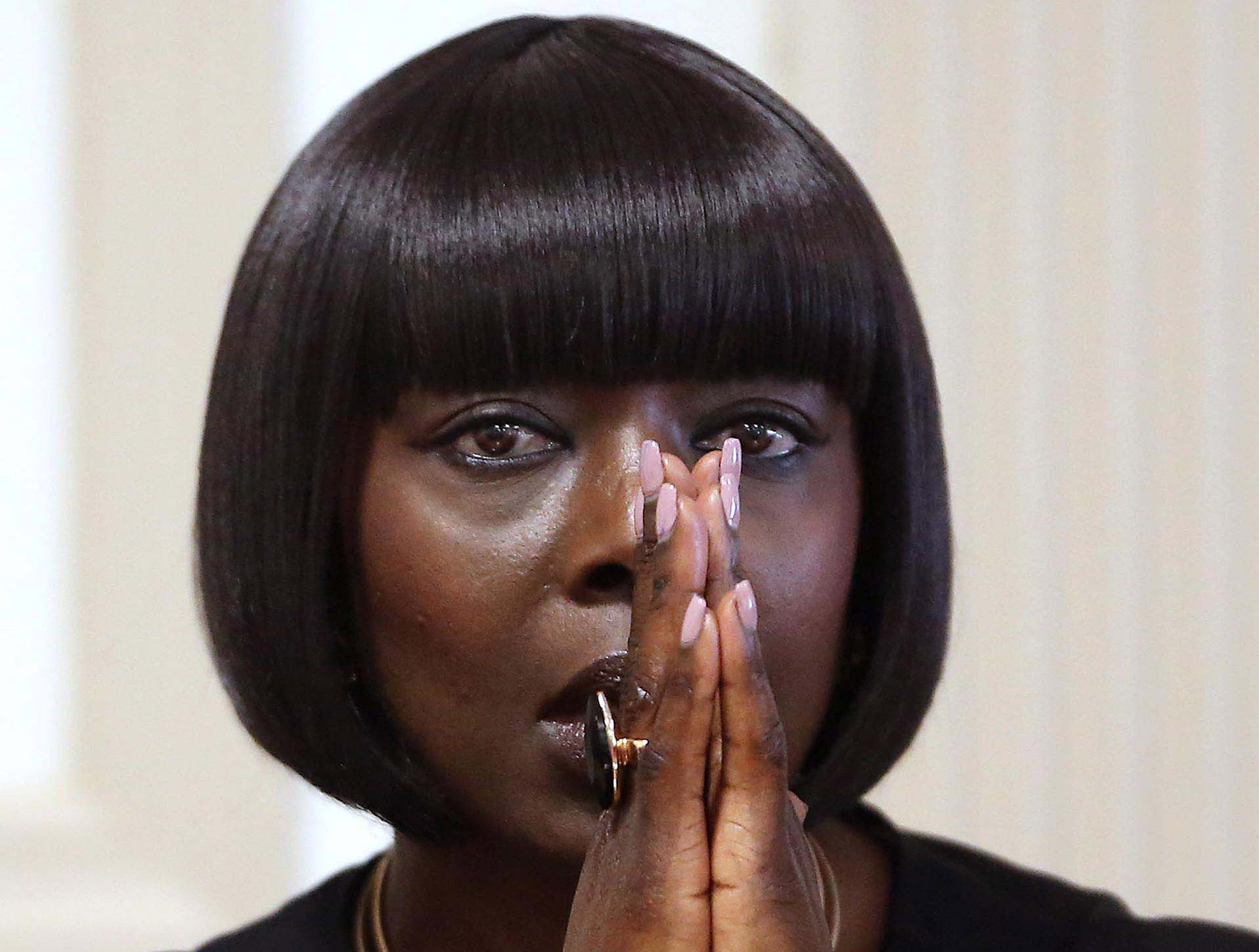 April 25, 2017--Mignone Njie, mother of Francis Thomas grasps her hand together in prayer as she is asked about the day of a violent struggle with her ex-boyfriend Edward Mendy. Her son, Francis Thomas is on trial for attempted murder of Mendy.
