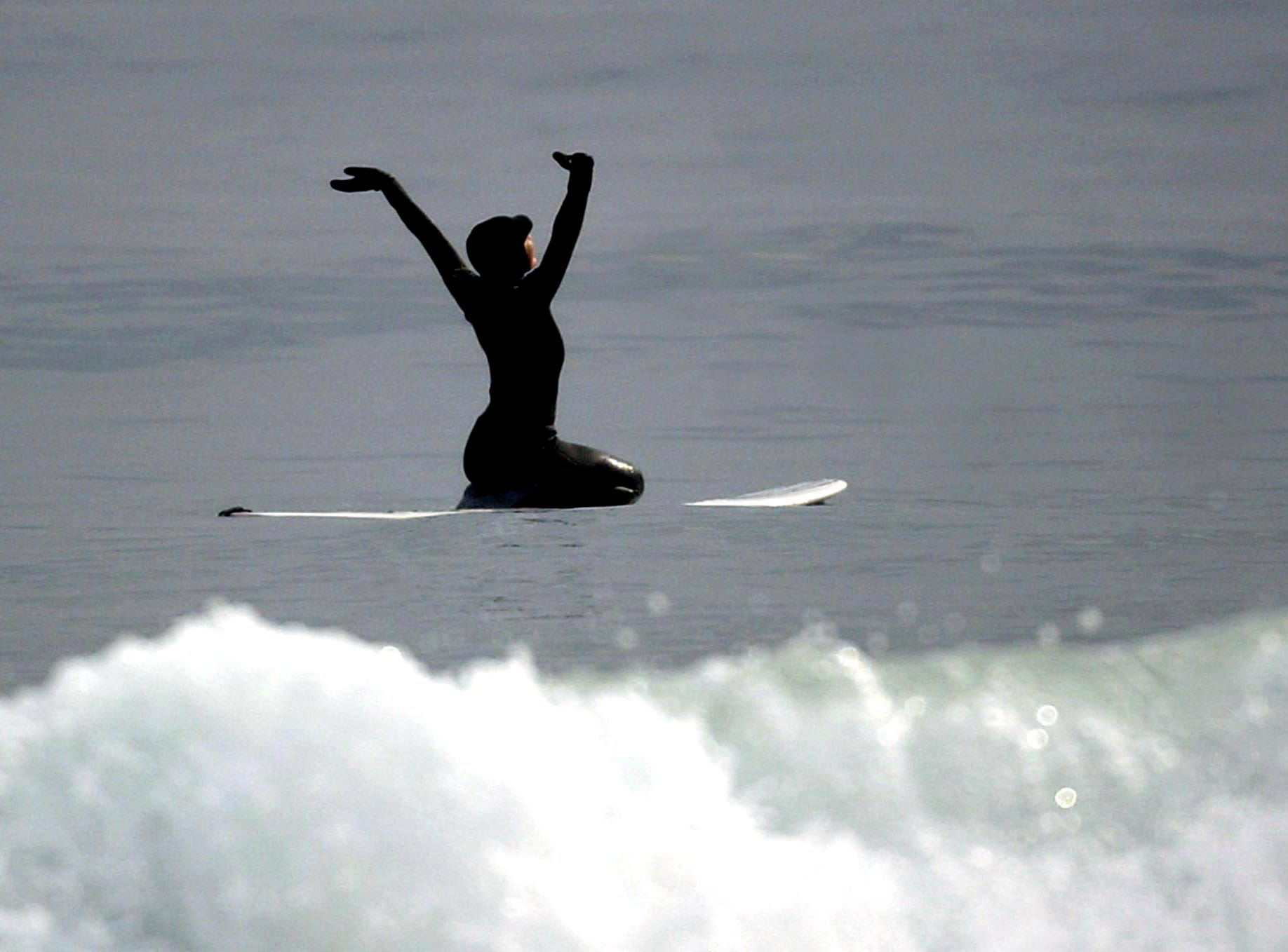 Surfer Stefanie Gallo reaches her arms towards the sky at Seaside Heights, New Jersey as she 'gives thanks,' a surfing tradition. February 5, 2005, Seaside Heights, New Jersey