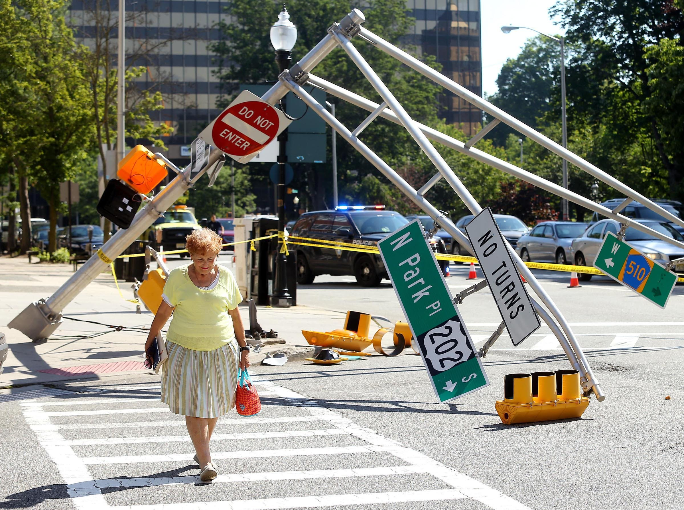 June 13, 2017--Geri Magala of Morristown crosses the street as traffic is rerouted in downtown Morristown after a truck took down a traffic light on the corner of N. Park Place and Washington Street.