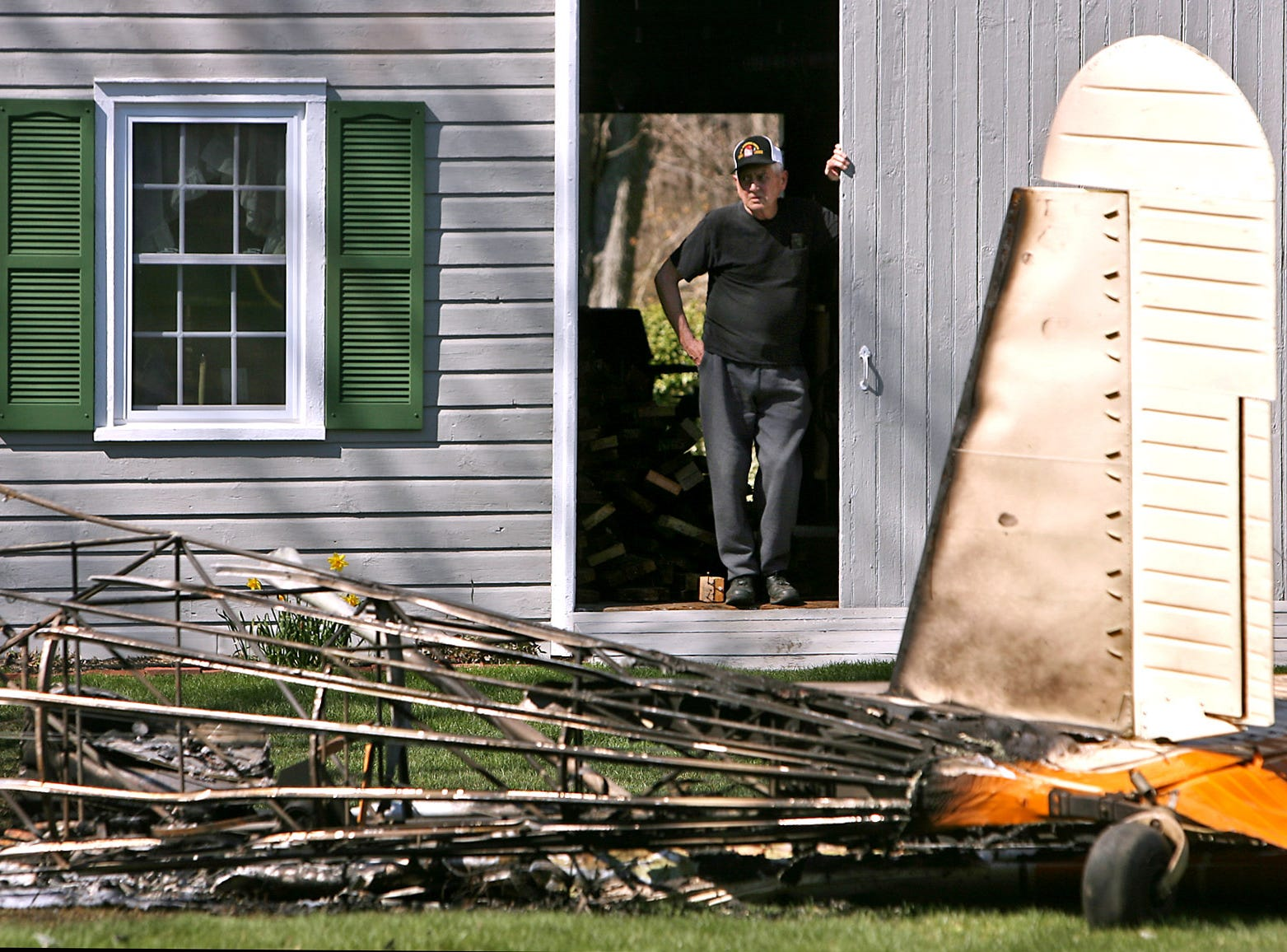 John Smith looks on from his barn at the wreckage of a small plane after a fiery crash shortly after takeoff from Lincoln Park Airport. April 20, 2007, Lincoln Park, NJ