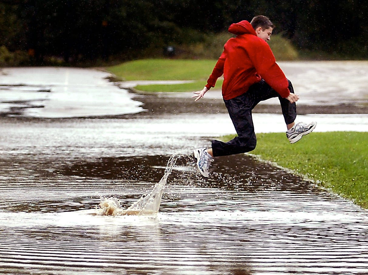 Roxbury, September 18, 2004--A high school cross country runner leaps across a flooded street as two friend wait their turn, on their way to the start line of the Roxbury Invitational Cross Country Meet.