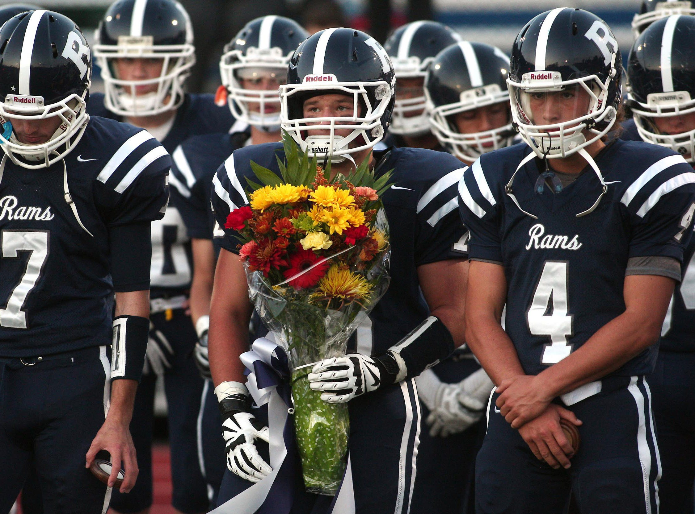 Randolph lineman George Zach holds a bouquet of flowers to give to the mothers of senior football players Jack Timmerman and Calvin Verduga who were killed in a single-car accident on Ironia Road in July during a tribute to the memories of the Randolph players at the first home game of the year, September 19, 2014, Randolph, NJ.