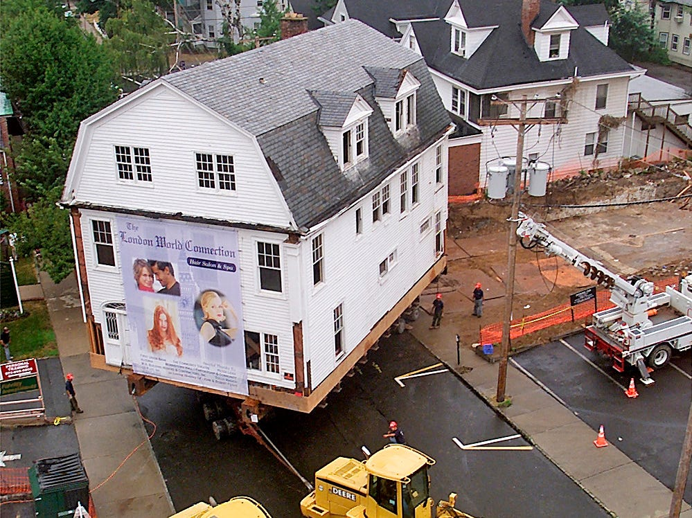 Morristown--08/24/02-  Workers from W. A. Building Movers and Contractors, Inc. guide A three-story Colonial revival style house on Pine Street as it is moved to its new site on DeHart Street after it was bought for $1.