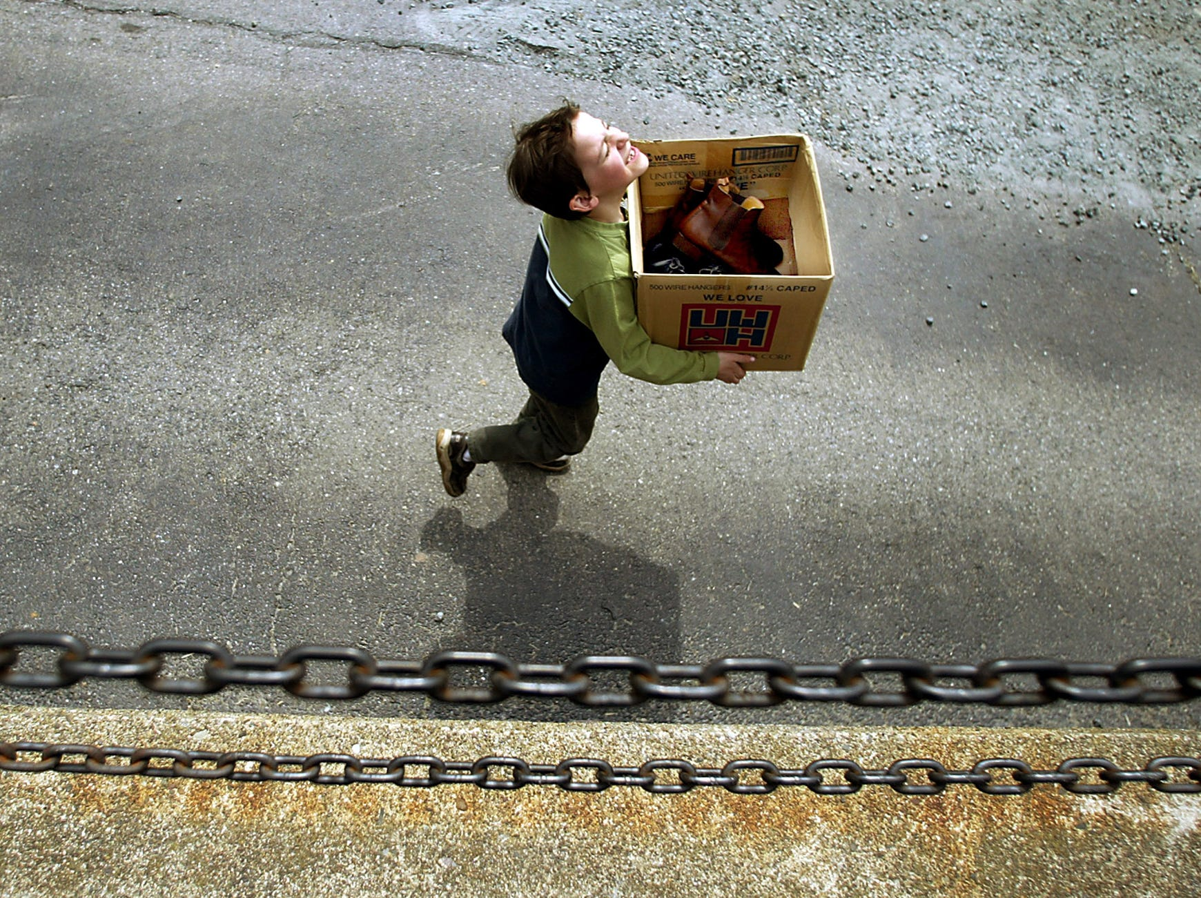 Trent Gardner, 7, laughs as he sprints down the driveway with a box of shoes to deliver to shipping and receiving after a fire destroyed the main building of Rago's, Morristown's historic shoemaker. April 8, 2004, Morristown, NJ