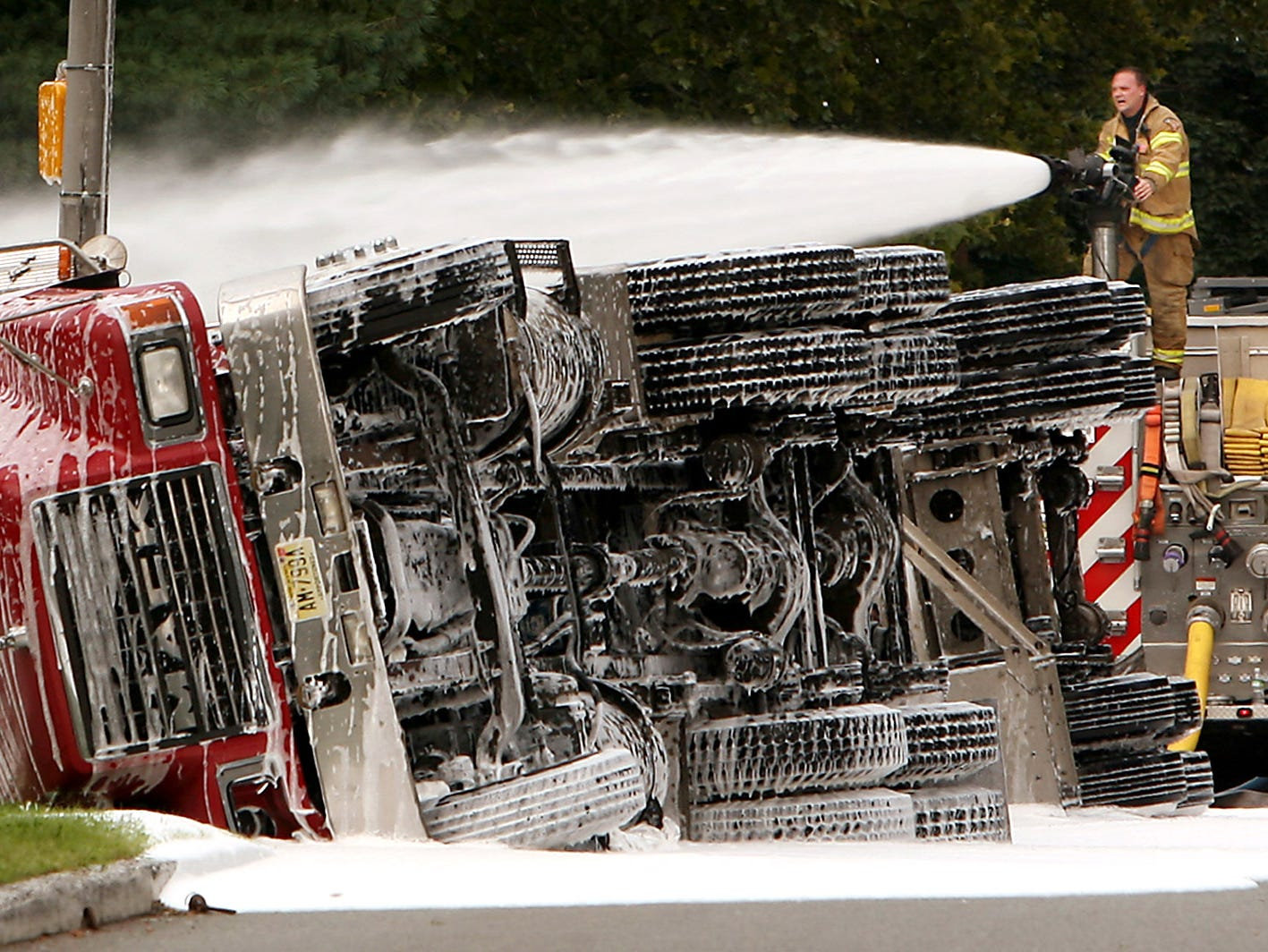 A firefighter sprays foam around an overturned gasoline tanker. August 5, 2009, Morristown, NJ
