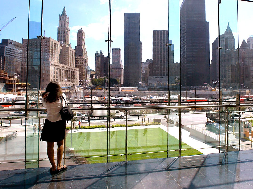 "Manhattan--Sept. 9, 2003--Holly Furman of NYC looks out at Ground Zero from the Winter Garden in the World Financial Center nearly two years after the World Trade Center attacks. Holly lived and worked in NYC at the time of the attacks and said she had not been back to the site of the attacks for about 1 1/2 years. She said, ""This is such a better image watching the rebuilding rather than all the destruction."""