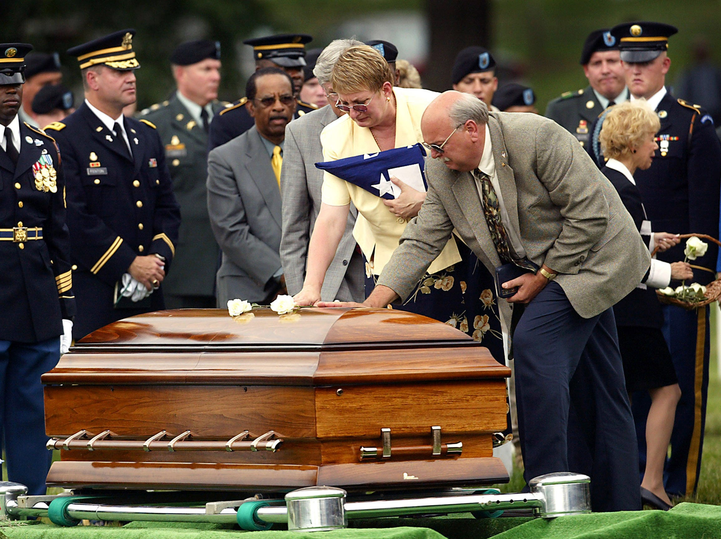 After leaving flowers, Cheryl and Raymond Doltz touch the casket of their son Ryan after his honors funeral at Arlington National Cemetery. Doltz, 26,  was killed in Baghdad, Iraq, when his vehicle hit an improvised explosive device.  June 16, 2004, Arlington, VA
