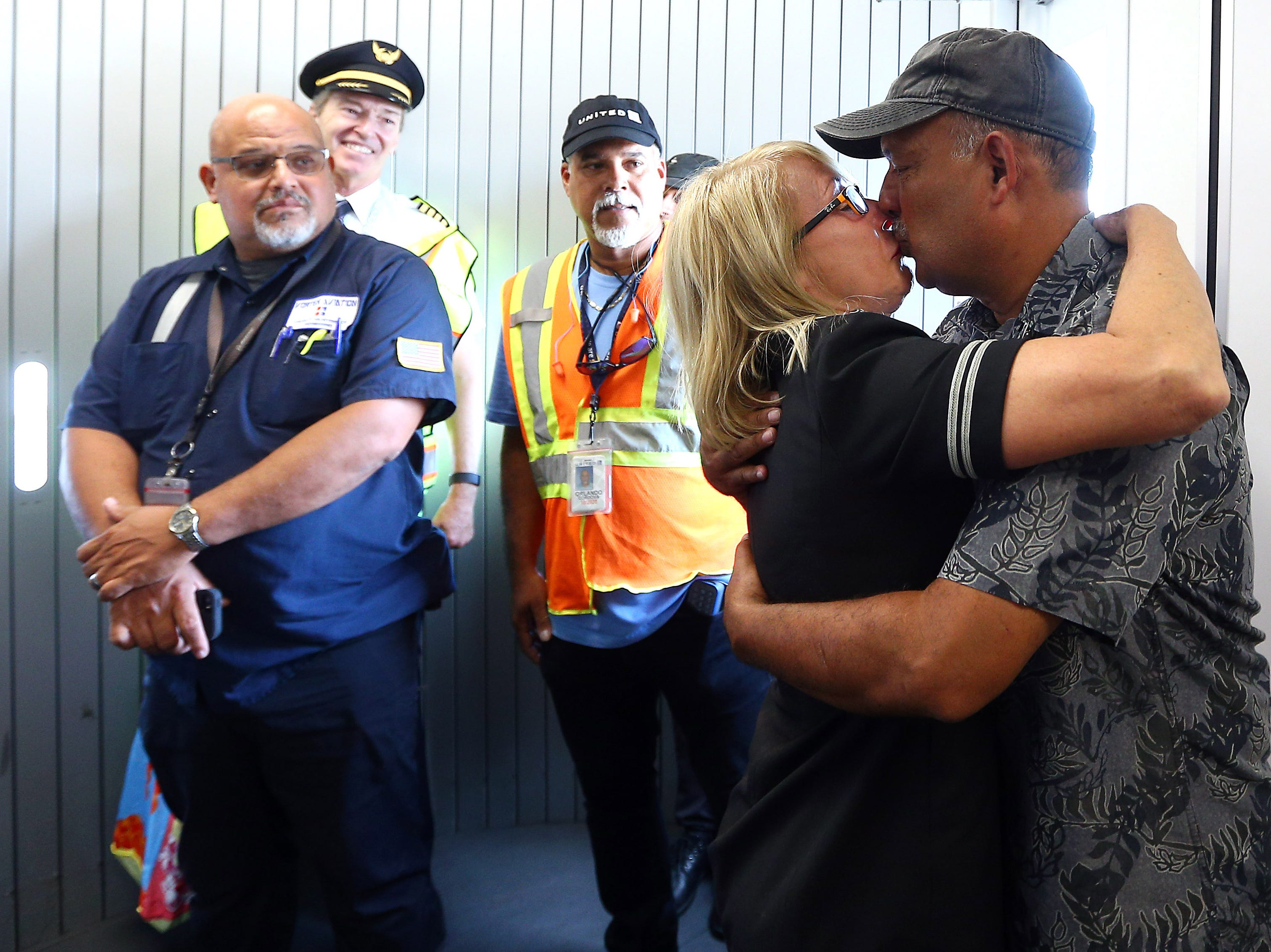 United Flight Attendant Bobbie Mas gets a kiss from her husband David Morales after the two were reunited at Luis Munoz Marin International Airport. Morales, a United pilot has been working with the Coast Guard in San Juan since 9/25 and surprised his wife who flew down Wednesday morning from Newark Liberty Airport. October 4, 2017, San Juan, Puerto Rico.