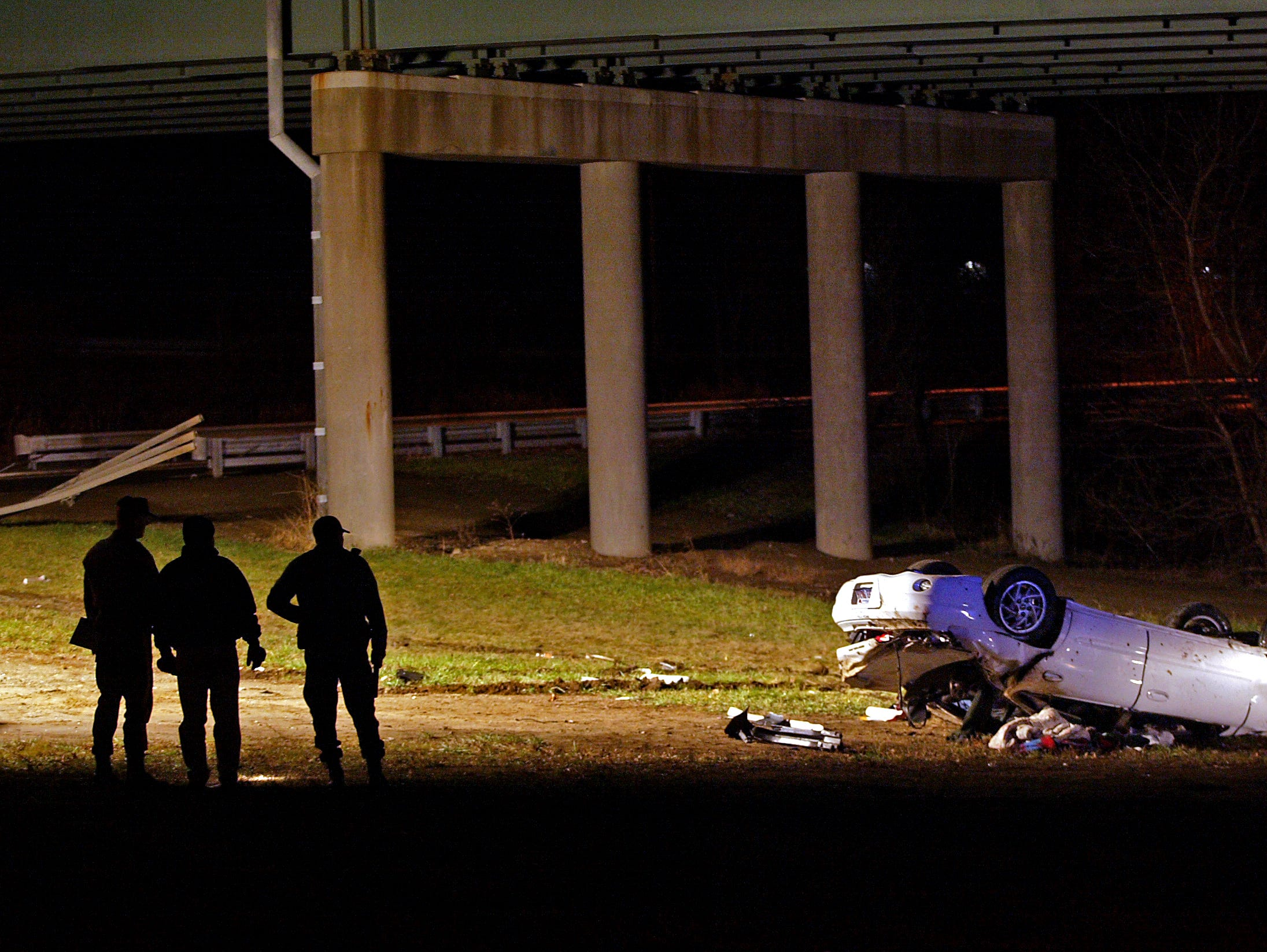 New Jersey State Police investigate the scene of an accident on Christmas night where a Chicago man crashed his Pontiac Grand Am through two guardrails on a Route 80 overpass. The car then plunged 40 feet landing upside-down on Route 46.
