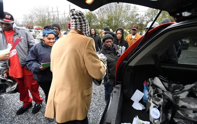Nate Calhoun, back to camera, with the Community 911 project, gives out bags containing blankets and warm clothes outside of the Friendship Mission in Montgomery, Ala., on Friday December 21, 2018.