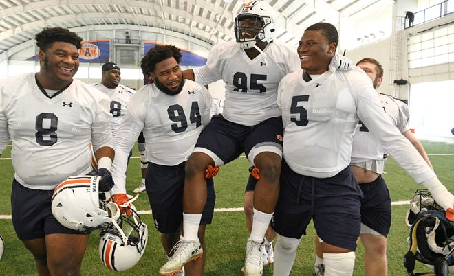Defensive tackle Dontavius Russell (95) is carried off the field after Auburn's last home practice on Wednesday, Dec. 19, 2018 in Auburn, Ala.
