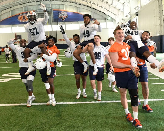 Linebackers Deshaun Davis (57), Darrell Williams (49) and Montavious Atkinson (48) are carried off the field by teammates, including K.J. Britt (far left) and Chandler Wooten (center-left) after Auburn's final home practice on Wednesday, Dec. 19, 2018 in Auburn, Ala.