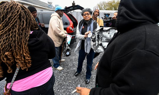 Kathy Martin, with the Community 911 project, gives out bags containing blankets and warm clothes outside of the Friendship Mission in Montgomery, Ala., on Friday December 21, 2018.