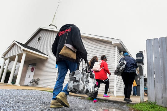 People in need carry bags, containing blankets and warm clothes, given to them as part of the Community 911 project outside of the Friendship Mission in Montgomery, Ala., on Friday December 21, 2018.