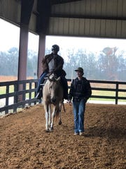 Joseph Bradley riding MANE horse, Nutty, with the guidance of volunteer Judd Hubbard.