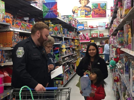 In this photo, a young girl picks out gifts for Christmas at the annual Cops and Kids event at the Walmart in Smyrna, Tenn. on Friday, Dec. 21, 2018.